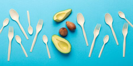 Say no to plastic, save the planet. Eco plastic of avocado seeds isolated on blue background, panorama Stock Photo