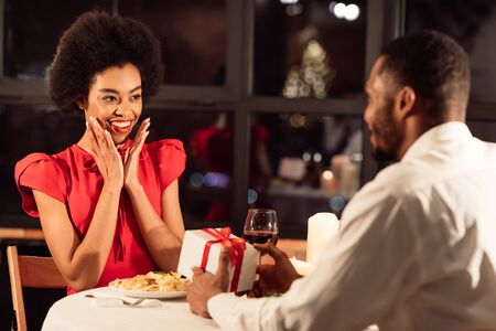 Valentines Day. African American Man Giving A Gift To Girlfriend Having Romantic Date In Restaurant. Selective Focus Stock Photo - 137213411