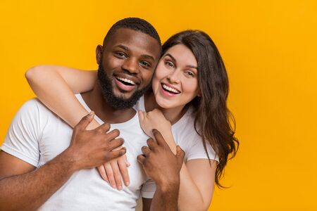 Portrait of romantic interracial couple hugging and looking at camera, posing together over yellow background, closeup