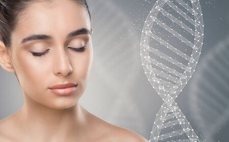 Pretty young woman with closed eyes next to DNA chain over grey background, modern beauty industry Stock Photo