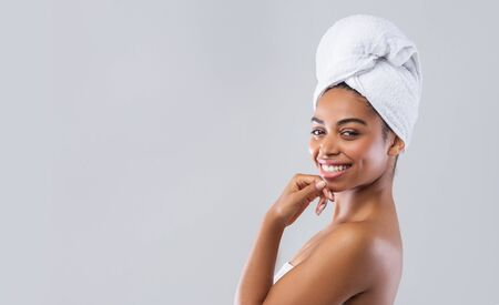 Profile portrait of pretty black lady wrapped in towel over grey background, panorama with free space