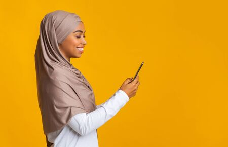 Profile portrait of cheerful black girl in hijab using smartphone, texting or browsing social media, yellow studio background with empty space