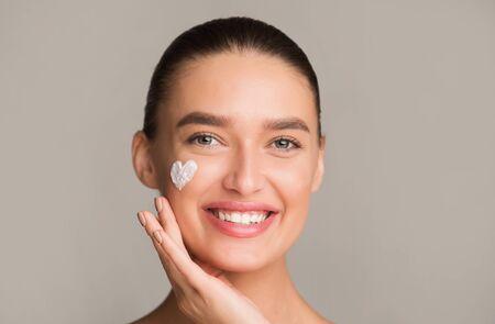 Skin hydration. Positive girl applying moisturizing cream in heart shape on cheek, grey background