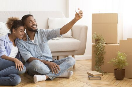 Happy Black Couple House Owners Making Selfie On Phone After Moving Into New Apartment. Free Space For Text