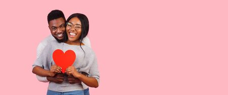 Be my valentine. Black couple in love embracing and holding big red shaped card, panorama with copy space Stock Photo - 137320786