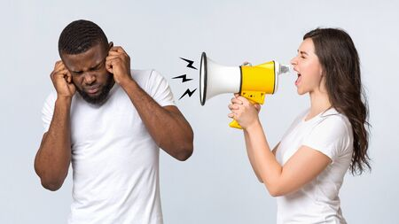 Angry woman shouting at her afro boyfriend with loudspeaker, having nervous breakdown or pms, standing together over light background, panorama