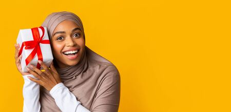 Happy african american girl in hijab holding gift box near ear, trying to guess whats inside, panorama with copy space