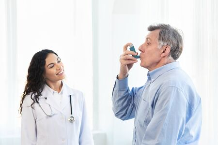 Consejo médico. Anciano con inhalador para el asma, médico mexicano mirando, espacio libre