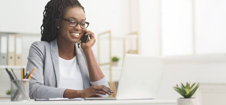 Lady Boss. Afro Businesswoman Talking On Cellphone While Working On Laptop In Modern Office, Wide Horizontal Banner, Panorama With Free Space Imagens