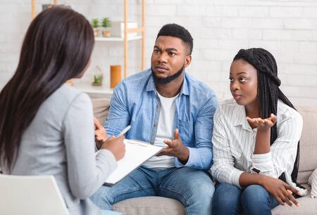Unexperienced psychologist. Young afro couple do not agree with counsellors conclusions, sitting on sofa and emotionally gesturing Reklamní fotografie
