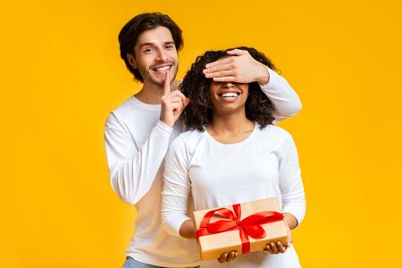 Guess who. Handsome guy covering his girlfriends eyes, giving her present and making shhh gesture on yellow background with free space Stock Photo - 137277011