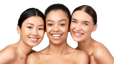 Three Multiracial Models Girls Posing Smiling At Camera Standing On White Studio Background. Skin And Body Care Beauty Concept. Panorama