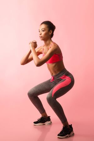 Fitness And Sport. African American Woman Doing Deep Squat Exercising On Pink Studio Background.