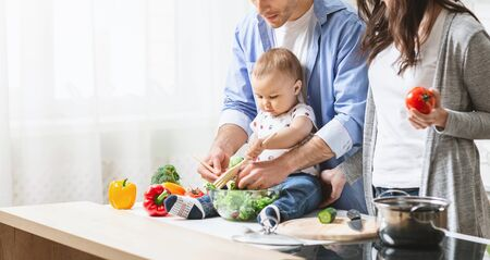 Fathers little helper. Adorable baby cooking vegetable salad with parents, sitting on kitchen table, panorama with empty space Stock Photo - 137322400