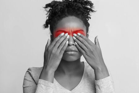 Monochrome photo of upset afro woman suffering from strong eye pain, covering her eyes with palms