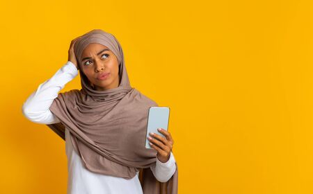 Forgot phone password. Thoughtful afro muslim girl holding smartphone and touching her head, not able to unblock her device, yellow blackground