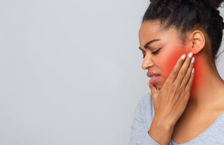 Sad young afro woman having wise teeth pain, touching her inflamed cheek, free space