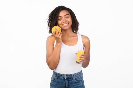 Healthy Diet. Happy black woman holding glass of tasty orange juice and fruit near face, white background, copyspace