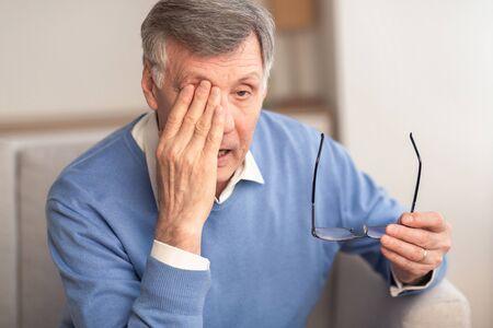 Jaskra. Zmęczony Starszy Mężczyzna Masuje Oko Trzymając Okulary O Zmęczenie Oczu I Napięcie Oczne Siedząc Na Kanapie W Domu. Selektywne skupienie