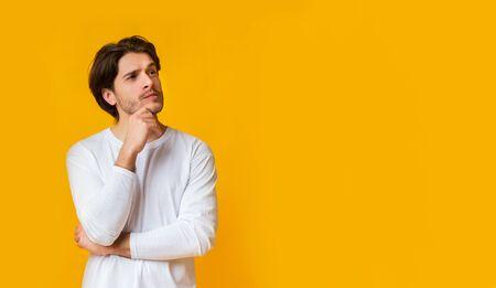 Retrato de joven dudoso pensando en algo, tocando la barbilla con expresión pensativa sobre fondo amarillo, espacio libre