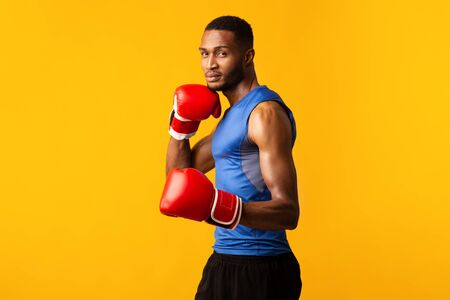 Boxing Stance. Muscular afro sports man in gloves looking at camera, yellow studio background, copyspace