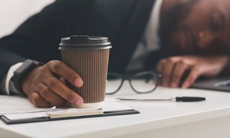 Coffee to go in sleeping young businessman hand, office interior, caffeine is the only way to survive, close up Stock Photo
