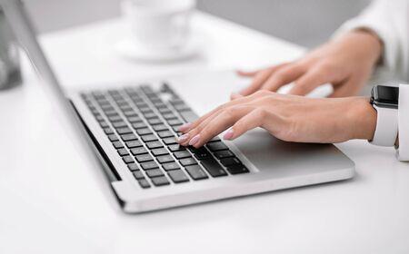 Freiberuflich. Nahaufnahme einer Frau mit Laptop, zu Hause arbeiten, einen Blog schreiben, die Hände auf der Tastatur. Exemplar Standard-Bild