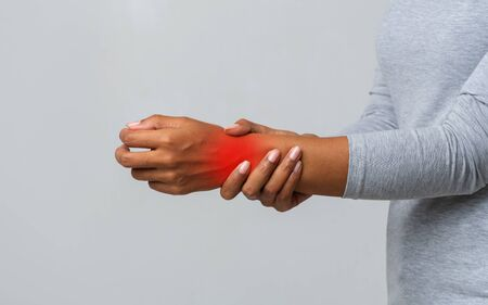 Cropped image of afro woman suffering from rheumatism, massaging her wrist, grey background
