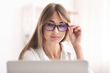 Schlechte Sicht. Business-Dame in Brillen mit zusammengekniffenen Augen auf Laptop-Bildschirm, der am Computer im modernen Büro arbeitet. Selektiver Fokus Standard-Bild