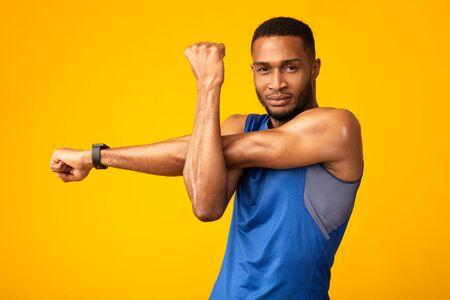 Calentamiento. Hombre afro musculoso estirando sus brazos y hombros antes de hacer ejercicio en el gimnasio sobre la pared amarilla del estudio, copyspace Foto de archivo