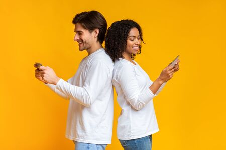 Gadget and social media addiction concept. Smiling multiracial couple standing back to back and using their smartphones, ignoring each other Stock Photo