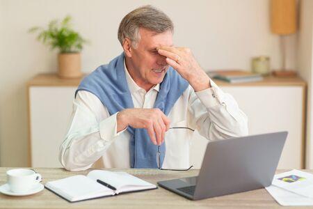 Überanstrengung der Augen im Alter. Älterer Mann massiert schmerzende Augen mit Brillen, die an Laptop-Computer im modernen Büro arbeiten. Selektiver Fokus