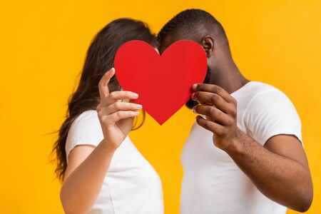 Happy Valentine's Day Concept. Romantic interracial couple kissing behind big red paper heart, standing together over yellow background Stock Photo - 137497682