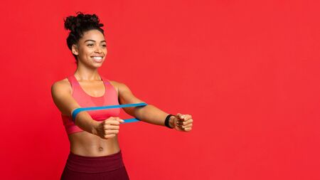 Sporty smiling black woman doing stretching work out with elastic bands, squating over red studio background, panorama with copy space Stock Photo