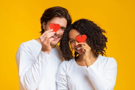 Sweethearts. Young Romantic Interracial Couple Covering Eyes With Red Paper Hearts In Their Hands, Yellow Background With Copy Space