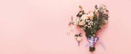 Wedding decor banner. Bride bouquet with boutonniere for groom and two golden rings on tender pink background, panorama with free space Foto de archivo