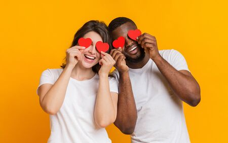 Lovebirds. Romantic multiracial couple posing with red hearts over eyes and laughing, standing together over yellow background with empty space