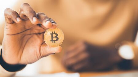 Digital Currency. African businessman holding golden bitcoin, close up of hand. Panorama, selective focus