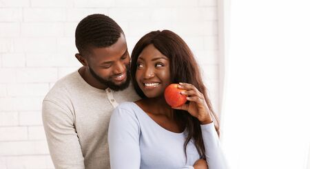 Happy afro woman with apple looking at her husband, man hugging woman from behind, white background, panorama with free space
