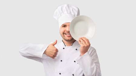 I Like Cooking. Positive Chef Man Gesturing Thumbs-Up Holding Plate Near Face Covering Eye Standing Over White Studio Background. Panorama Stok Fotoğraf