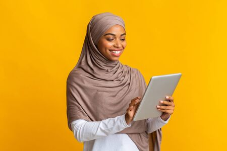 Portrait of smiling afro muslim girl in hijab using digital tablet, downloading new app or browsing media, standing over yellow background, free space Foto de archivo
