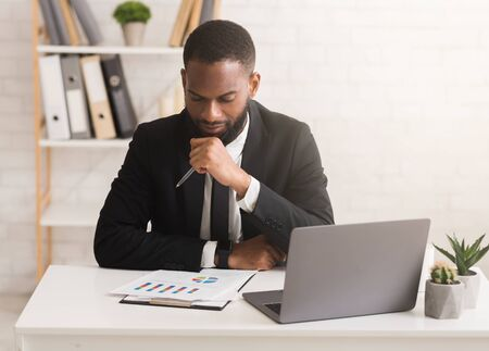 Serious african american businessman working on financial report in modern office, free space