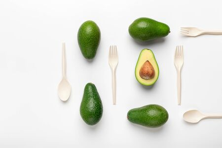 Creative flat lay of avocados and biodegradable Single-Use Cutlery isolated on white background, copy space Stock Photo