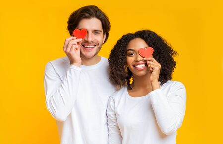 True Love. Portrait of happy interracial couple with red paper hearts over eyes posing together over yellow background, free space