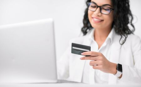 Shopping Online. Happy mexican woman making purchases, selective focus on plastic credit card. Copy space