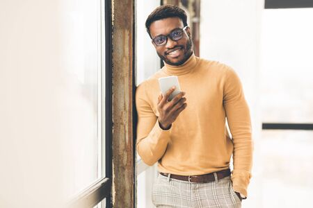 Young Entrepreneur. Smiling black businessman holding phone, looking at camera standing by window. Empty space