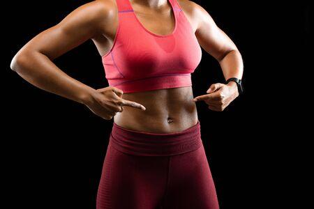 Cuerpo sexy de modelo de fitness femenino africano apuntando a sus músculos abdominales sobre fondo negro, paquete de seis
