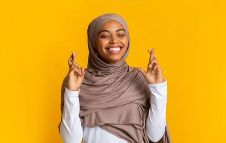 Cherished wish. Portrait of positive afro muslim woman in hijab pleading for something with crossed fingers and closed eyes over yellow background Foto de archivo