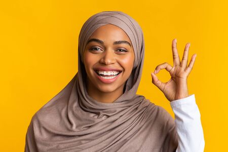 Its OK. Closeup portrait of joyful black muslim girl in hijab gesturing okay sign and sincerely laughing over yellow background Banque d'images - 137804061