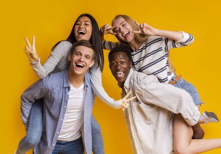 Two international student couples having fun over yellow background, posing on camera, making piggy-back